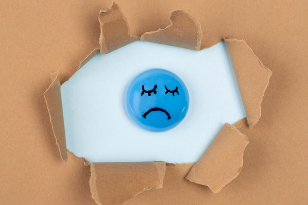 Top view of sad balloon in torn paper for blue monday