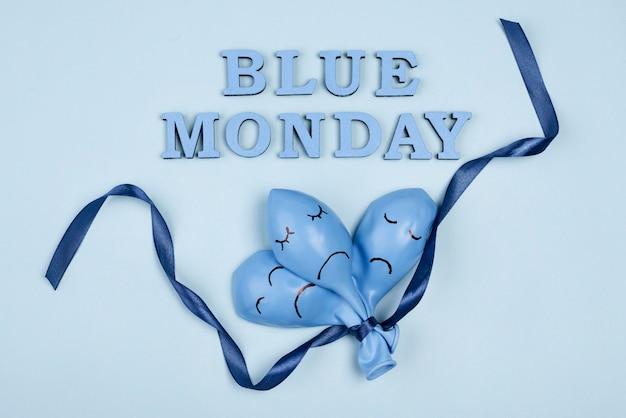 Top view of sad blue monday balloons with ribbon