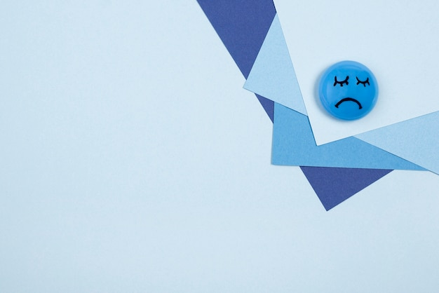 Top view of sad face for blue monday with paper