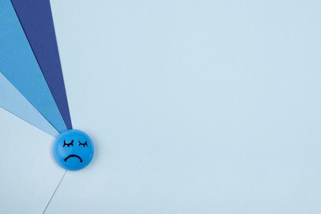 Vista dall'alto della faccia triste con carta per lunedì blu