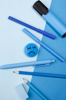 Top view of sad face with pencils and marker for blue monday