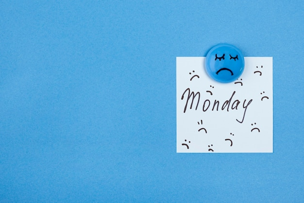 Top view of sad face with sticky note and copy space for blue monday