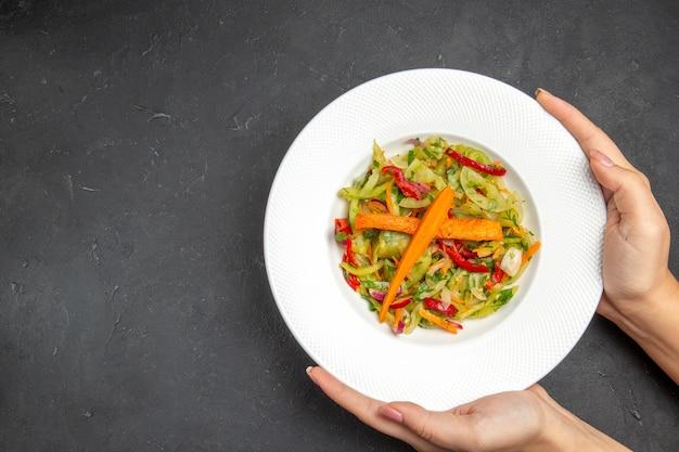 Vista dall'alto di insalata un'insalata appetitosa con verdure nel piatto in mano