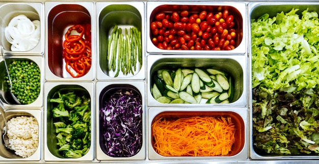 Top view of salad bar with assortment of ingredients for healthy and diet meal.