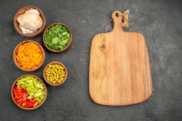 ダークテーブルの健康サラダダイエット食品に鶏肉と緑のトップビューサラダ材料