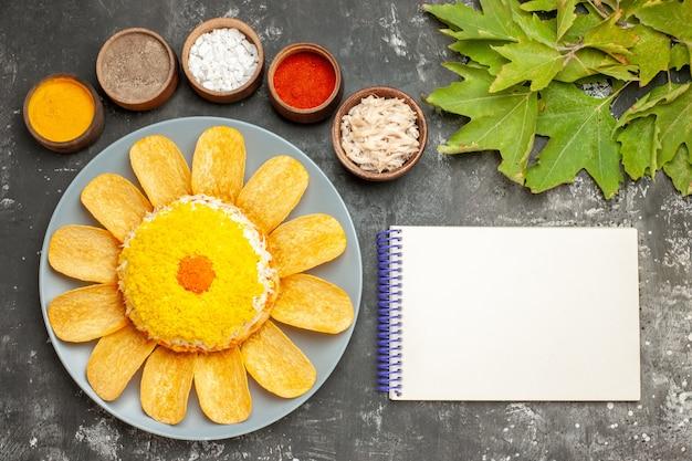 Vista dall'alto di insalata sul lato sinistro con erbe aromatiche e blocco note sul lato con foglie sul lato destro sul tavolo grigio scuro