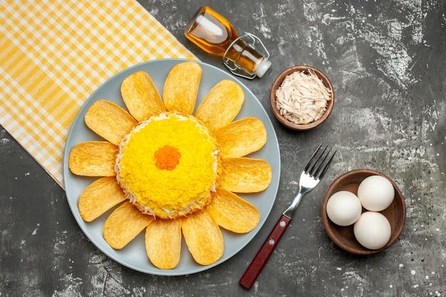 Vista dall'alto di insalata sul lato sinistro con tovagliolo giallo sotto di esso con bottiglia di olio di forchetta di formaggio e ciotola di uova sul lato sul tavolo grigio scuro