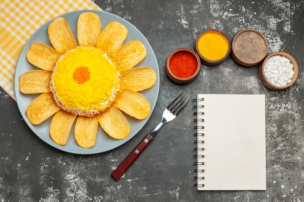 Vista dall'alto di insalata sul lato sinistro con tovagliolo giallo sotto con blocco note di erbe e forcella sul lato sul tavolo grigio scuro