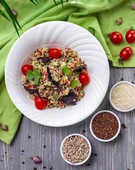 Вид сверху салат из семян кунжута, льна и подсолнечника с помидорами и базиликом