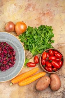 텍스트를 위한 공간이 있는 나무 테이블에 있는 로마 토마토 당근 감자와 양파와 같은 신선한 재료가 근처에 있는 세라믹 접시에 있는 탑 뷰 샐러드