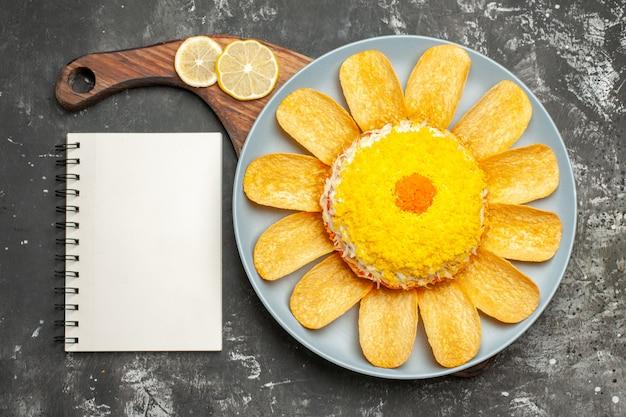 Vista dall'alto di insalata su supporto piatto con limone e blocco note sul lato sul tavolo grigio scuro