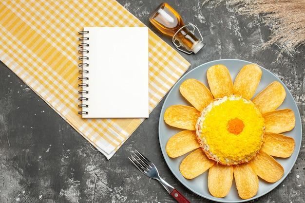Vista dall'alto di insalata sul lato destro con grano di forchetta bottiglia di olio tovagliolo giallo e blocco note sul lato sul tavolo grigio scuro