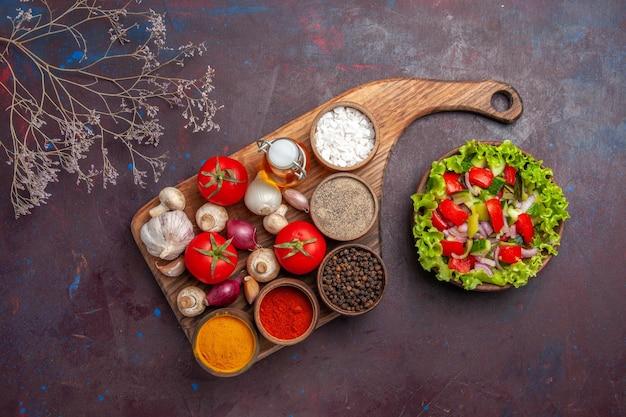 Vista dall'alto insalata e spezie spezie diverse pomodori funghi cipolle sul tagliere e insalata con verdure