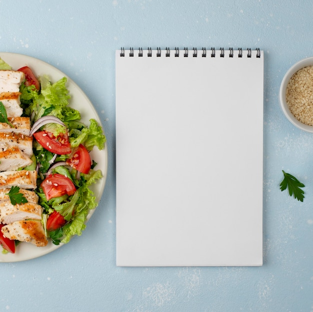 Top view salad with chicken and blank notepad