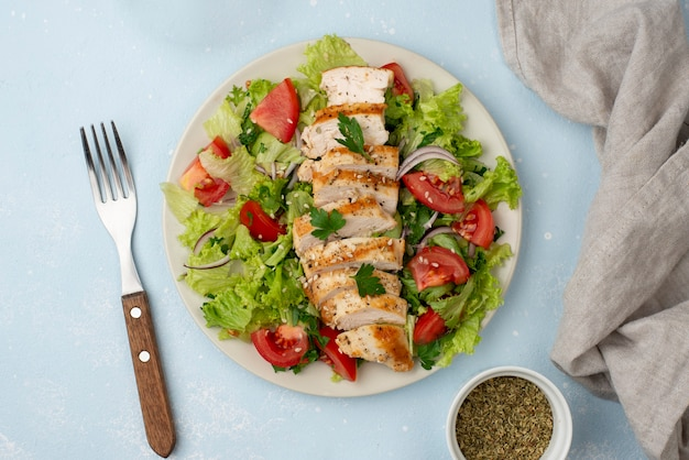 Top view salad with chicken, herbs and fork