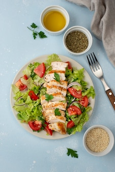 Top view salad with chicken, herbs and oil