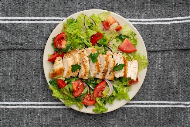 Салат с курицей и кухонным полотенцем вид сверху