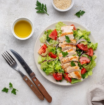 Top view salad with chicken, sesame seeds and oil