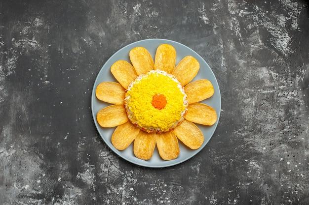 Vista dall'alto di insalata con patatine intorno sulla piastra su sfondo scuro