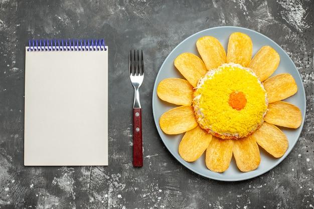 Vista dall'alto di insalata con patatine fritte con forchetta e blocco note dal lato sinistro su sfondo scuro