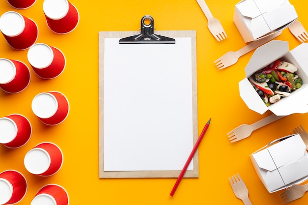 Top view salad with clipboard on yellow background