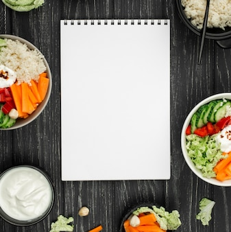 Top view salad with couscous and blank notebook