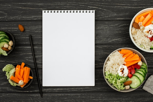 Top view salad with couscous and blank notepad