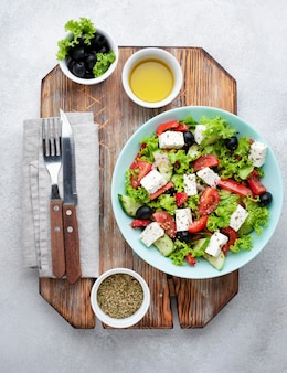Top view salad with feta cheese on cutting board with olives and herbs