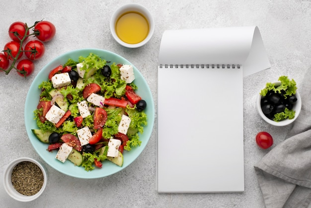 Top view salad with feta cheese, tomatoes and olives with blank notepad