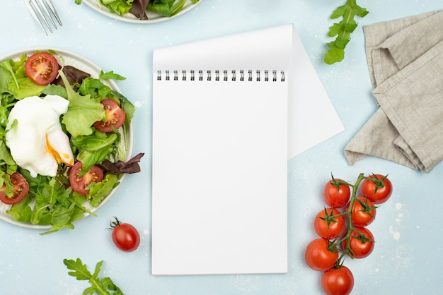 Top view salad with fried egg and tomatoes with blank notepad