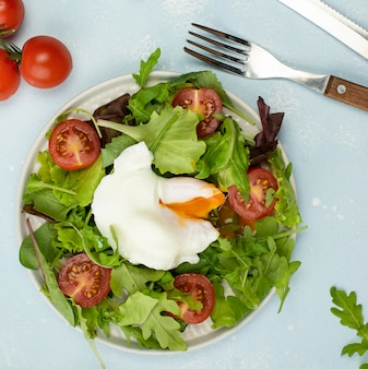Top view salad with fried egg and tomatoes