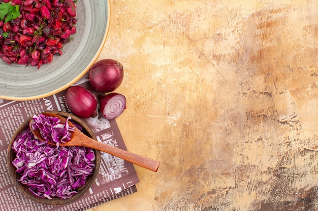 左側にコピー場所がある木製のテーブルの上に刻んだキャベツと玉ねぎのボウルで作られた緑の葉と野菜のトップビューサラダ