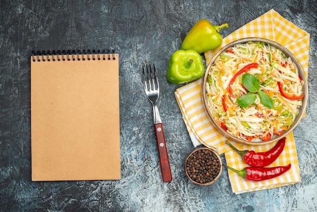Vista dall'alto di insalata con ingredienti e taccuino sulla superficie scura