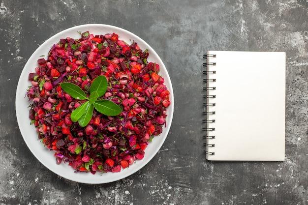 灰色の背景に白い皿に赤い野菜のトップビューサラダ