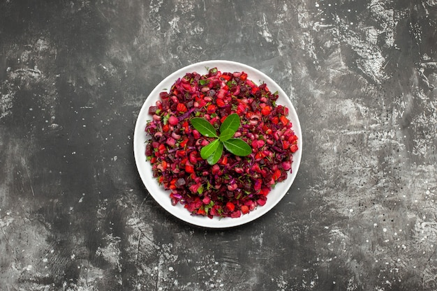 Top view salad with red vegtable in a white dish on grey background