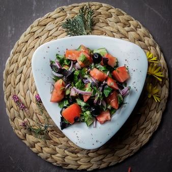 Insalata di vista dall'alto con pomodoro, cetriolo, lattuga, cipolle, olive in un piatto bianco su un supporto di vimini