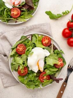 Салат с помидорами и жареным яйцом с вилкой, вид сверху
