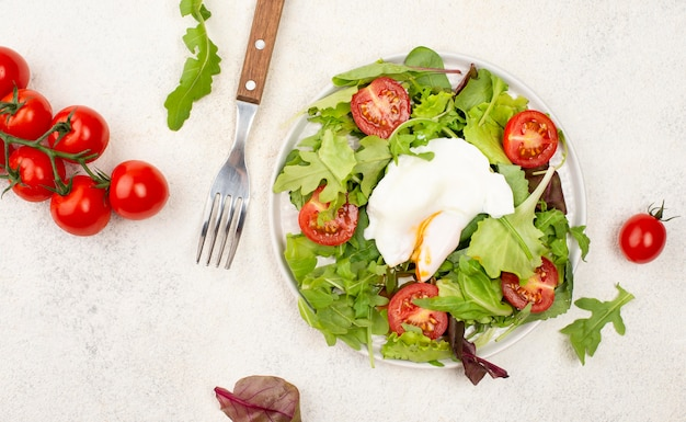 Top view salad with tomatoes and fried egg