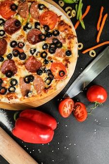 黒いテーブルにナイフトマトオリーブとピーマンのスタンドに平面図サラミピザ