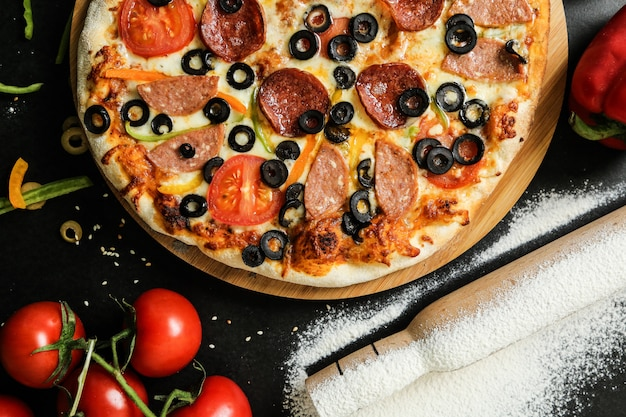Top view salami pizza on stand with knife tomatoes olives and bell pepper on black table