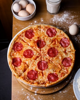 Top view of salami pizza with cheese and pepperoni on a wooden table