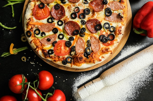 Top view salami pizza with tomatoes bell peppers and olives on a tray with flour and rolling pin