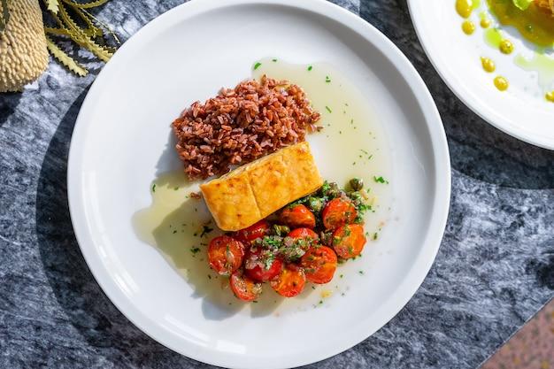 Вид сверху филе лосося на гриле с булгуром с помидорами на мраморном столе