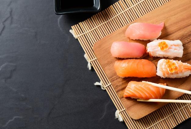 Top view of salmon sushi nigiri in chopsticks