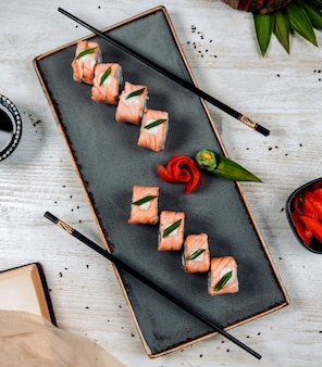Top view of salmon sushi topped with cream and onion slice