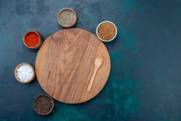 Вид сверху соль и перец с другими приправами на темно-синем столе для ингредиентов.
