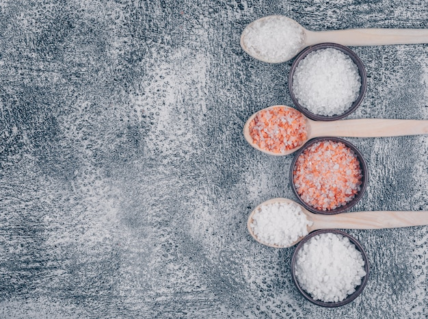 Top view of salt in bowls and wooden spoons with himalayan salt
