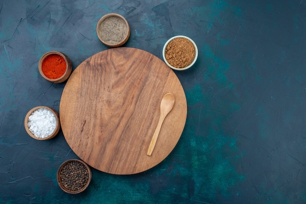 Vista dall'alto sale e pepe con altri condimenti sullo scrittorio del pepe dell'ingrediente di superficie blu scuro