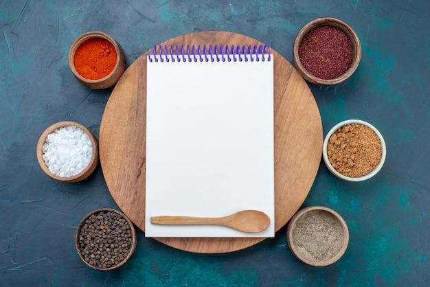 Vista dall'alto sale e pepe con altri condimenti e blocco note sullo scrittorio del pepe degli ingredienti di superficie blu scuro