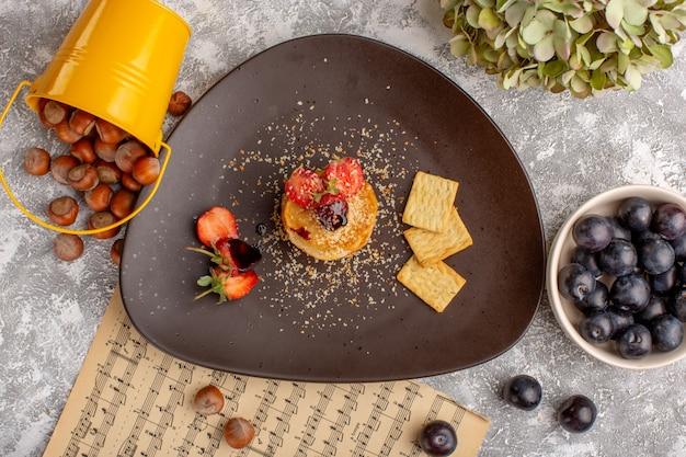 Вид сверху соленые чипсы с клубникой внутри тарелки вместе с терновником на белом столе, чипсы, закуска, фруктовые ягоды